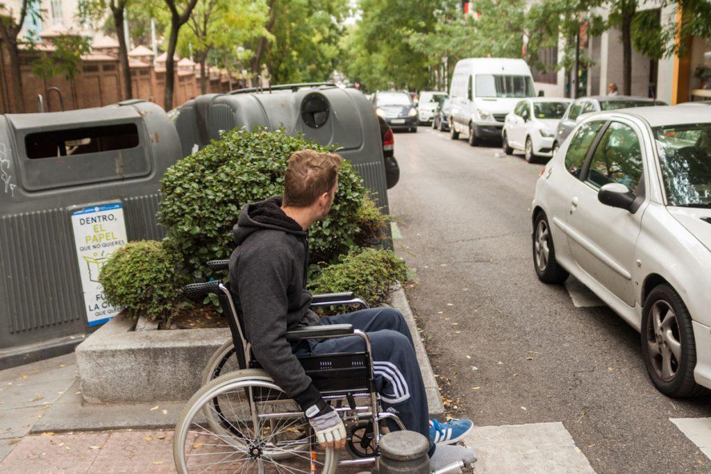 Setos y contenedroes no permiten la vidibilidad del cruce a una persona en silla de ruedas.