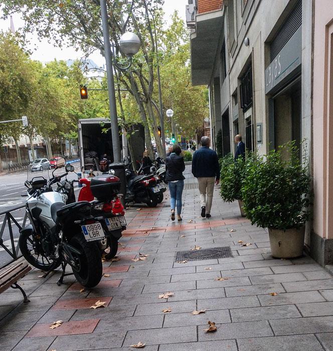 Macetas en fachada y motos en línea de bordillo
