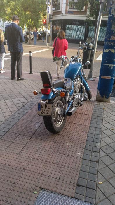 Moto aparcada sobre paso de peatones.
