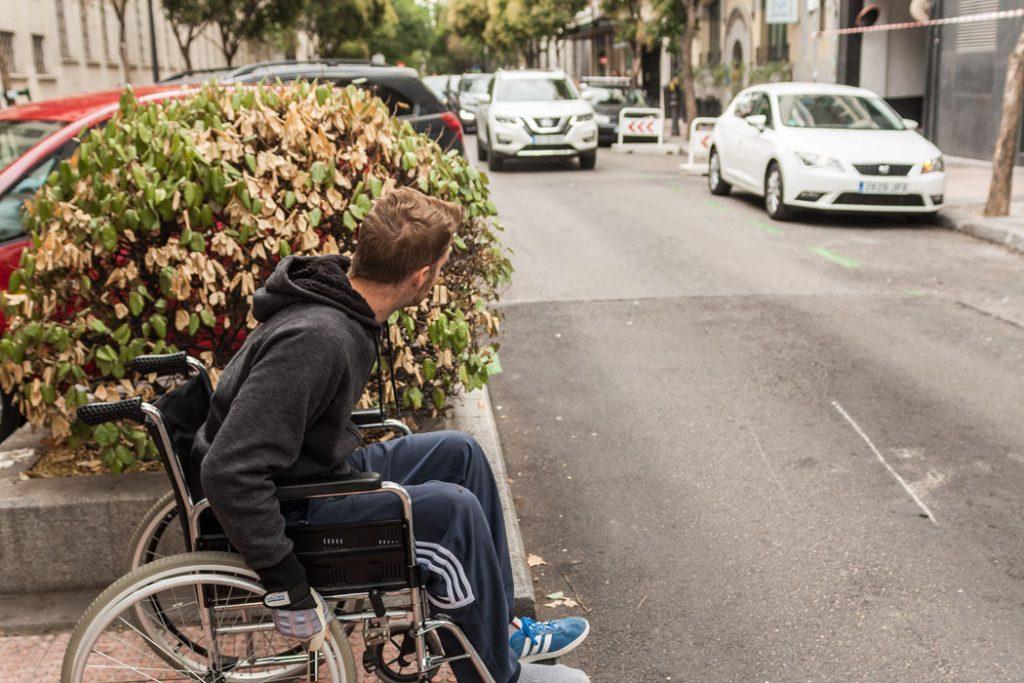 Persona en silla de ruedas con dificultsades para cruzar por falta de visibilidad por culpa de un gran seto.